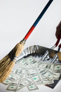 Broom sweeping US currency into dust pan